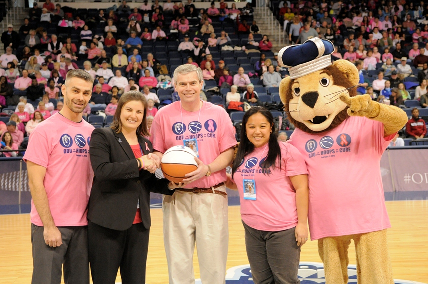 Dr. Jason McHugh, Dr. Michael Simpson, and Dr. Jocelyn Ricasa (all in pink) accept the game ball.